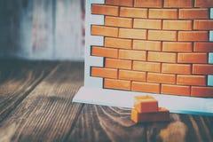 Muurspeelgoed en rode bakstenen heb het stemmen Het concept onroerende goederenaankoop en voltooiing van bouw Geen geld en nr stock fotografie