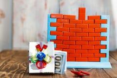 Muurspeelgoed en rode bakstenen heb het stemmen Het concept onroerende goederenaankoop en voltooiing van bouw Geen geld en nr stock foto