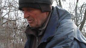 Muy un viejo hombre pasa a trav?s de los tableros para reparar una choza o encender el fuego, vida despu?s de la guerra almacen de metraje de vídeo