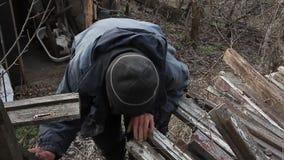 Muy un viejo hombre pasa a trav?s de los tableros para reparar una choza o encender el fuego, vida despu?s de la guerra metrajes