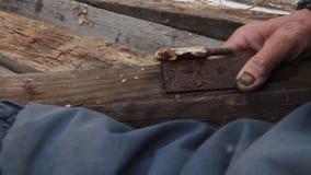 Muy un viejo hombre pasa a trav?s de los tableros para reparar una choza o encender el fuego, vida despu?s de la guerra almacen de video
