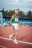 Muy viejo atleta que corre abajo del estadio de la pista Fotos de archivo
