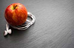 Muziek het spelen appel waarin de oortelefoons worden aangesloten royalty-vrije stock afbeeldingen