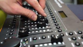 Muziek of lichte technologie, handen die mengt console in geluidsopnamestudio gebruiken stock video