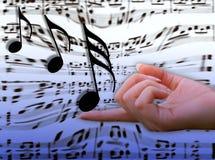Muziek op haar vinger stock fotografie