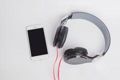 Muziekconcept - smartphone en hoofdtelefoons op witte achtergrond Royalty-vrije Stock Afbeeldingen