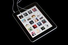 Muziekspeler op ipad met oortelefoons Royalty-vrije Stock Foto