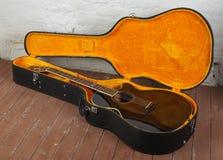 Muzikaal instrument - bruine schema akoestische gitaar in hard geval royalty-vrije stock afbeeldingen