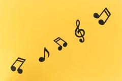 Muzikale achtergrond Nota's over een gele achtergrond Royalty-vrije Stock Foto's