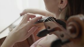 Muzikale ambacht door positieve vrouwelijke violoncellist bij camera in lichte ruimte stock videobeelden