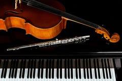 Muzikale instrumenten die op de piano liggen Stock Fotografie