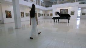 Muzikale pianistgang aan piano in een concertzaal steadycam Schot stock videobeelden