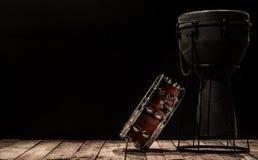 Muzikale slaginstrumenten op zwarte trommel als achtergrond Bongo en strik Stock Foto's