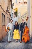 Muzikale triomensen op een oude Europese straat De band bestaat uit twee mensen en één meisje Mensen met dubbele baarzen en a Stock Foto