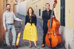 Muzikale triomensen op een oude Europese straat De band bestaat uit twee mensen en één meisje Mensen met dubbele baarzen en a Stock Fotografie