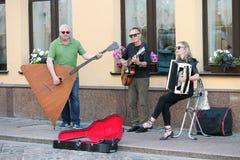 Muzikale triomensen op een oude Europese straat De band bestaat uit twee mensen en ??n meisje Mensen met dubbele baarzen en a royalty-vrije stock fotografie