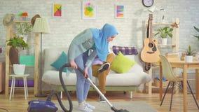 Muzułmańska kobieta w hijab vacuuming nowożytnego mieszkanie i używa smartphone, młodego człowieka obsiadanie na leżance zbiory