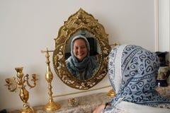 Muzułmańska dziewczyna z zakrywającą głową w błękitnym szaliku śmia się i ono uśmiecha się i spojrzenia w lustrze fotografia stock