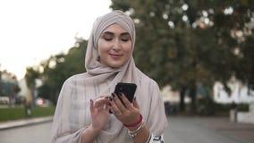 Muzułmańska piękna kobieta w pastelowym hijab z makeup pozycją na ulicznym mienia smartphone podczas gdy spacer w zbiory