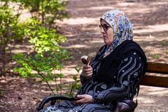 Muzułmańska stara kobieta relaksuje na ławce i je lodowego wkuwanie Zdjęcia Stock