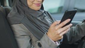 Muzułmański żeński kierowca używa telefon w ruchu drogowego dżemu podczas gdy wtykający, ryzyko wypadek zbiory