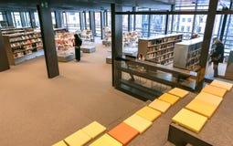 Muzułmański kobiety czytanie wśrodku nowej biblioteki publicznej De Krook z półka na książki i holem Zdjęcie Stock