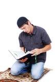 Muzułmański mężczyzna modleniem jest mienia holly książką Qoran i zdjęcia royalty free