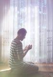Muzułmański mężczyzna ono modli się salowy przy ciemnym pokojem z jaskrawym okno światłem Zdjęcie Royalty Free