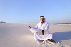 Muzułmański męski architekta obsiadanie z laptopem na piasku w pustyni na h Zdjęcia Stock