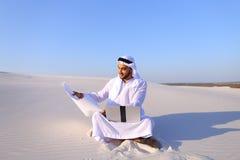 Muzułmański męski architekta obsiadanie z laptopem na piasku w pustyni na h Obrazy Royalty Free