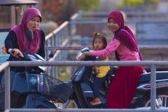 Muzułmańskie Kambodżańskie kobiety na motocyklach przy SIEM PRZEPROWADZAJĄ ŻNIWA dzielnicy miasta Zdjęcia Stock