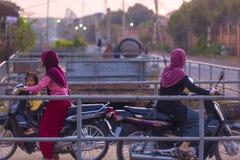 Muzułmańskie Kambodżańskie kobiety na motocyklach przy SIEM PRZEPROWADZAJĄ ŻNIWA dzielnicy miasta Zdjęcia Royalty Free