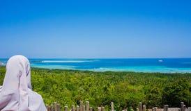 Muzułmańskiego dziewczyna zegarka palmowa lasowa zieleń, głęboki błękitny morze i plaża w karimun jawy wyspie fotografia stock