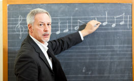 Muzycznego nauczyciela writing notatki na blackboard obraz royalty free
