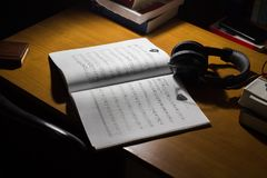 muzycznego prześcieradła hełmofony na biurku i gitara fotografia stock