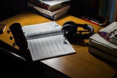 muzycznego prześcieradła hełmofony na biurku i gitara fotografia royalty free