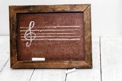 Muzyczny postaci i treble clef rysujący w kredzie na zarządzie szkoły zdjęcie stock