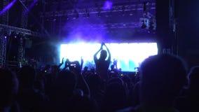 Muzyczny zespołu spełnianie na iluminującej scenie, sylwetki fan cieszy się przedstawienie zdjęcie wideo