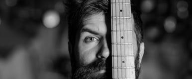 Muzyk, artysta na twarzy i gitary szyi zadumanej, spokojnej, Mężczyzna z brodą i wąsy zakrywa połówkę twarz z gitary szyją Obraz Stock