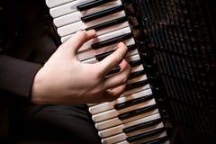 Muzyk bawić się akordeon przeciw ciemnemu tłu zdjęcia royalty free