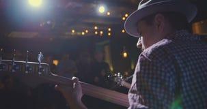Muzyk - gitarzysta w kapeluszu bawić się gitarę w noc klubie, tylni widok Fotografia Stock