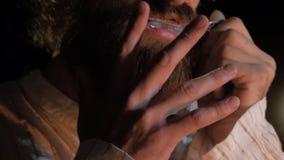Muzyk który bawić się etnicznych instrumenty Brodaty mężczyzna bawić się żyd ` s harfę Mężczyzna bawić się harfy zbliżenie Zdjęcie Stock