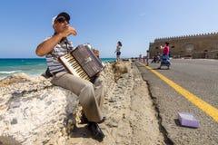 Muzyk na nabrzeżu bawić się akordeon obraz royalty free