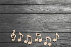 Muzyk notatki i treble clef na drewnianym tle, odgórny widok fotografia stock