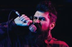 Muzyk, piosenkarza śpiew w hali koncertowej Mężczyzna z agresywną twarzą trzyma mikrofon, śpiewacka piosenka, Fotografia Royalty Free
