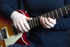 Muzyk w czarny bawić się na gitarze elektrycznej Fotografia Stock