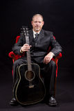 Muzyk w garnituru obsiadaniu w czerwonej aksamitnej krzesła mienia gitarze Zdjęcia Royalty Free