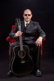 Muzyk w garnituru obsiadaniu w czerwonej aksamitnej krzesła mienia gitarze Obrazy Stock