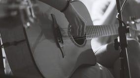 Muzyk w noc klubie czarny i biały - gitarzysta bawić się błękit gitarę akustyczną zakończenie, niezwykle up - Zdjęcia Stock