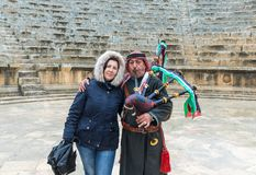 Muzyk w obywatel odzieżowych sztukach pozy, kobza i - Jerash, Gera Romański miasto w ruinach w Południowym Theatre z turystą obrazy royalty free